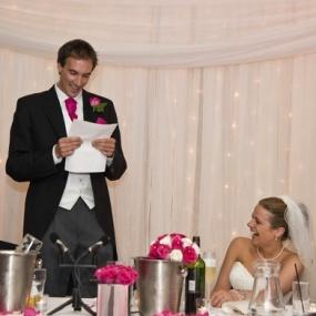 bräutigam liest von einem blatt eine vorbereitete rede ab und braut lacht dazu