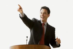 mann steht hinter rednerpult, hält vortrag und zeigt mit dem Zeigefinger der rechten Hand schräg nach oben